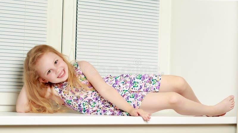 Uma menina está sentando-se pela janela com jalousie imagem de stock