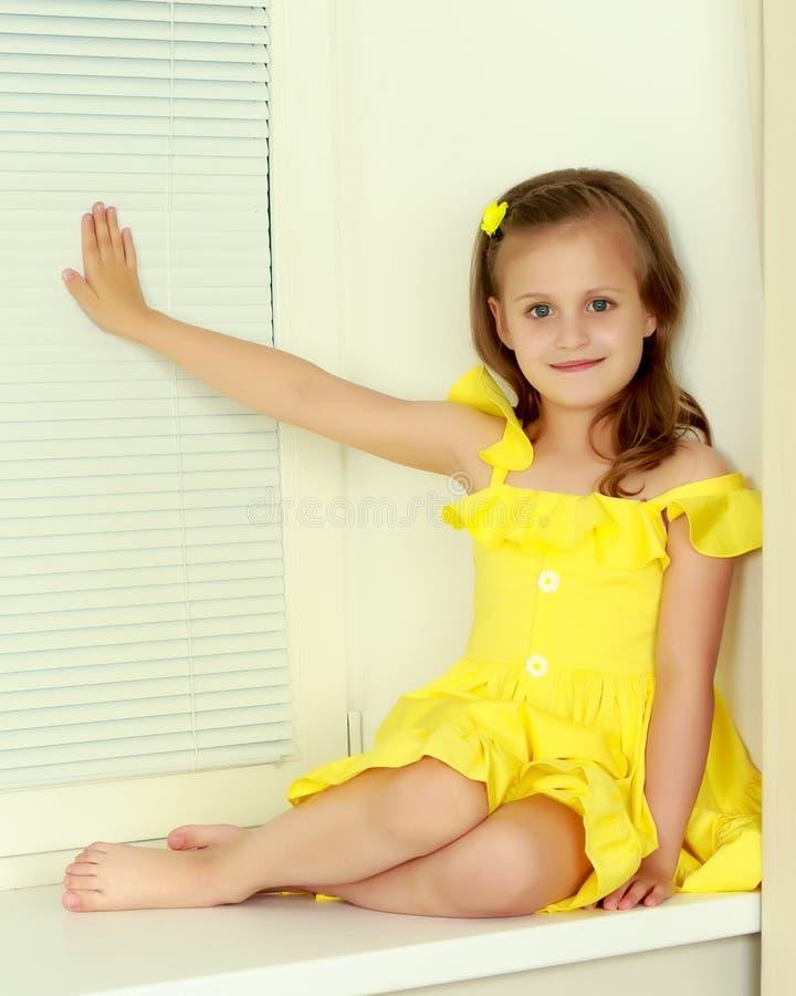 Uma menina está sentando-se pela janela com jalousie fotografia de stock royalty free