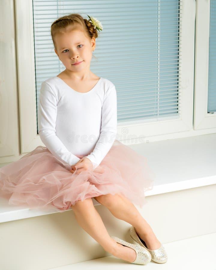 Uma menina está sentando-se pela janela com jalousie fotos de stock