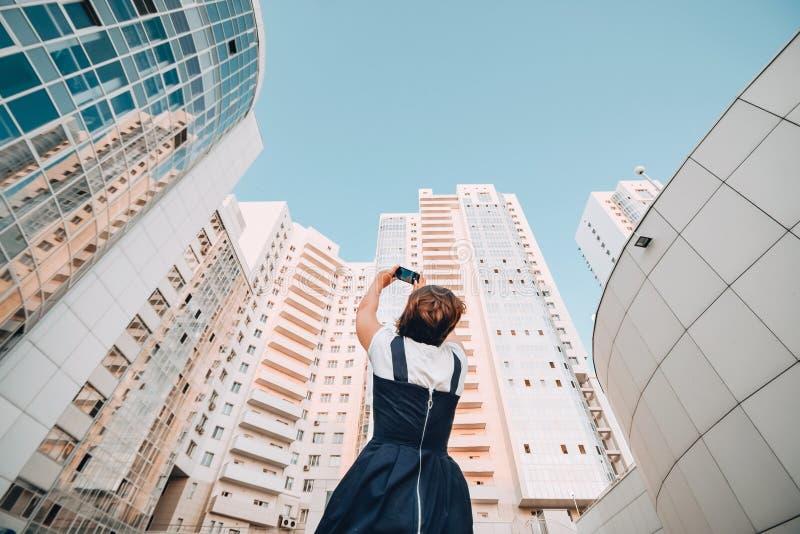 Uma menina está tomando imagens de um complexo residencial novo Arranha-céus modernos brancos Novos domicilios foto de stock royalty free