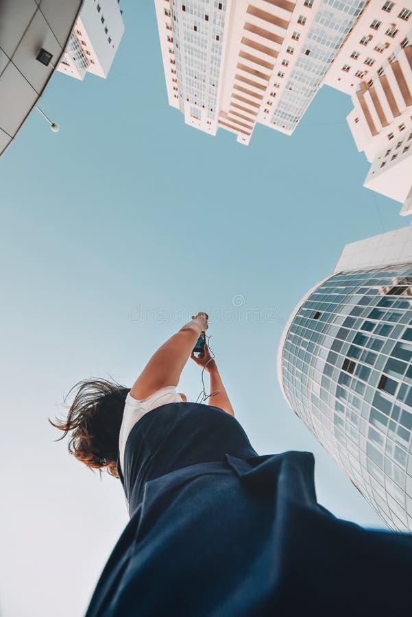 Uma menina está tomando imagens de um complexo residencial novo Arranha-céus modernos novos brancos fotos de stock