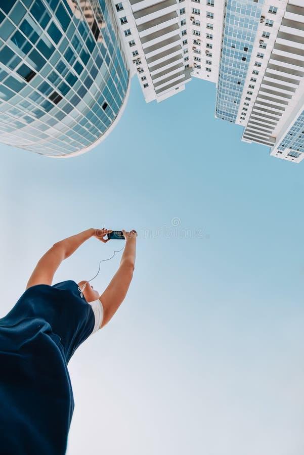 Uma menina está tomando imagens de um complexo residencial novo Arranha-céus modernos novos brancos fotografia de stock royalty free