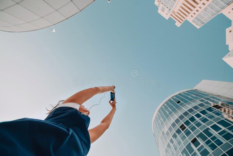 Uma menina está tomando imagens de um complexo residencial novo Arranha-céus modernos novos brancos imagem de stock royalty free