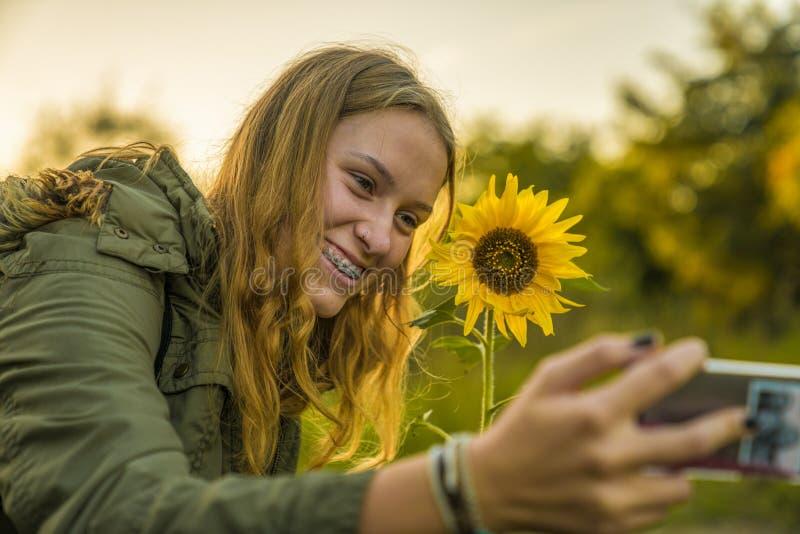 Uma menina está tomando um selfie com um girassol imagens de stock