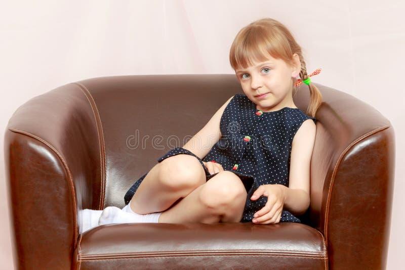 Uma menina est? sentando-se em uma cadeira de couro imagens de stock royalty free