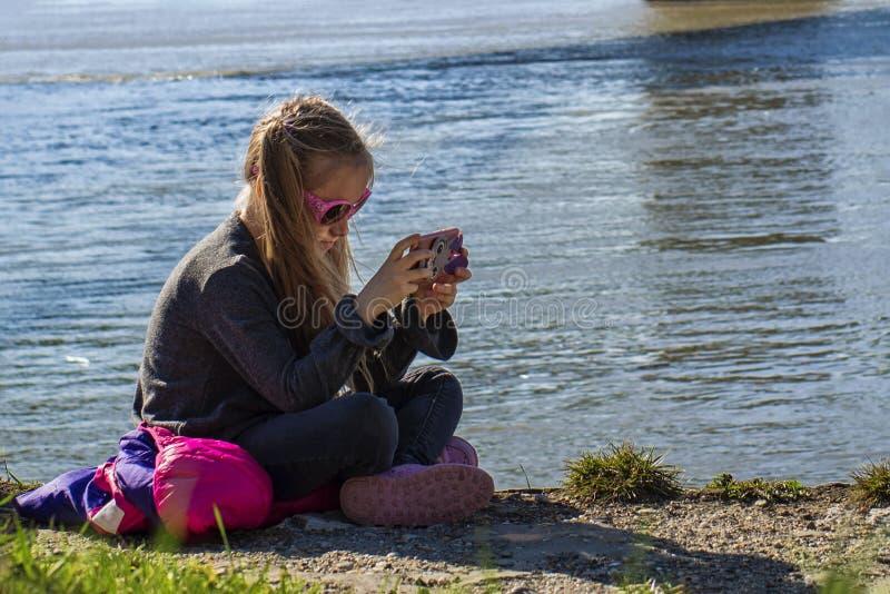 Uma menina est? sentando-se no banco do rio com um telefone Em um dia de mola morno fotos de stock royalty free