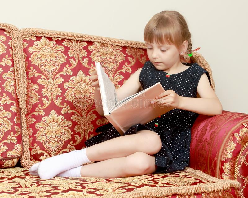 Uma menina est? sentando-se no sof? e est? lendo-se um livro imagem de stock royalty free