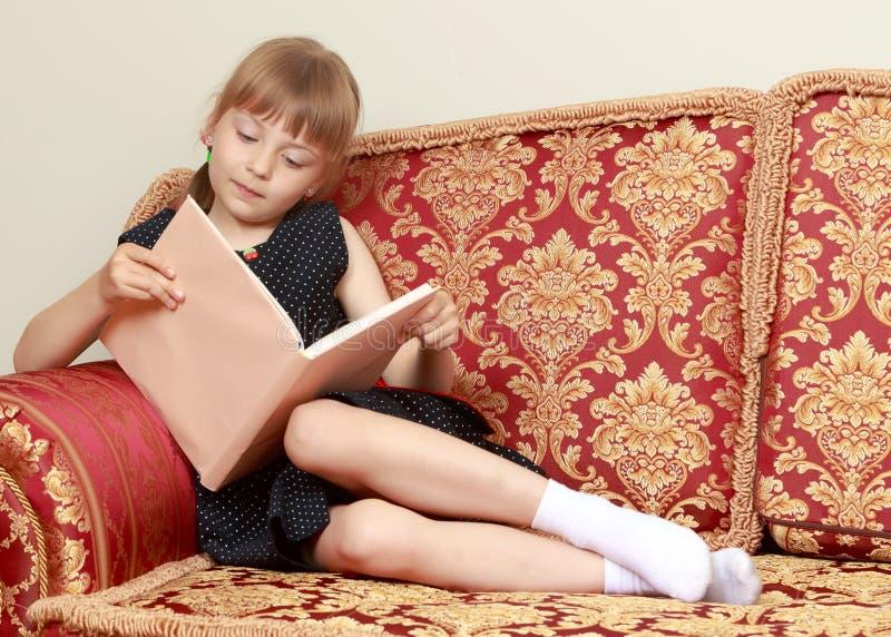 Uma menina est? sentando-se no sof? e est? lendo-se um livro foto de stock