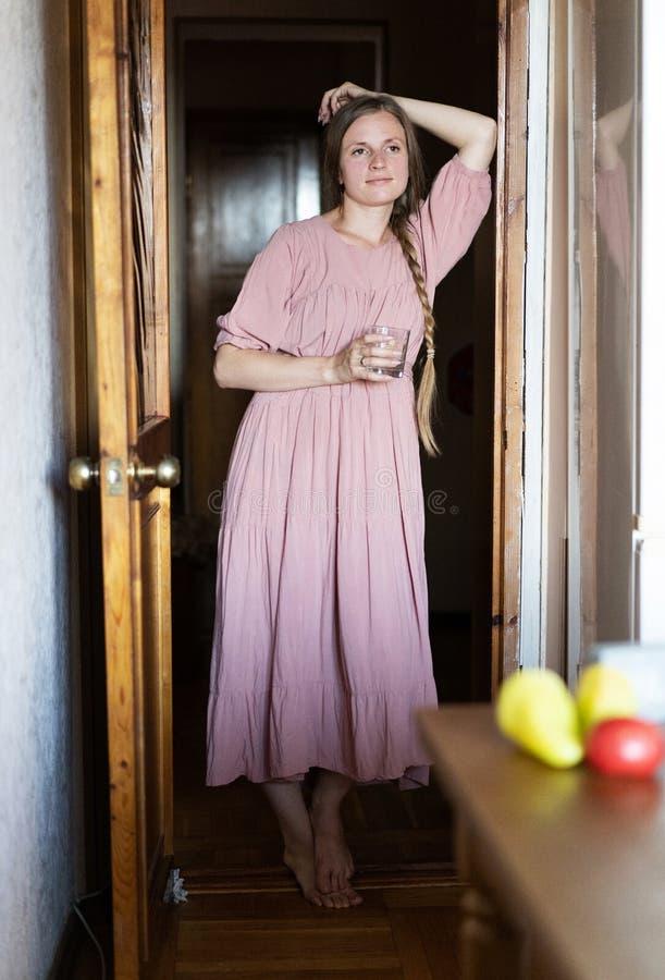 Uma menina europeia bonito em um vestido cor-de-rosa está estando na entrada e está guardando uma caneca Retrato com a face surpr fotos de stock royalty free