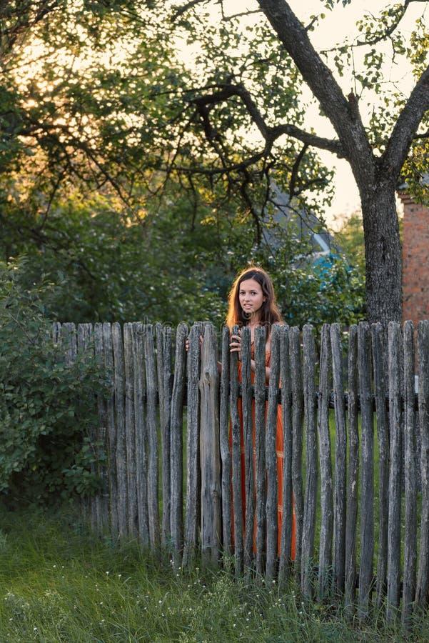 Uma menina expectante triste está atrás de uma paliçada de madeira em um vestuário da vila fotos de stock royalty free