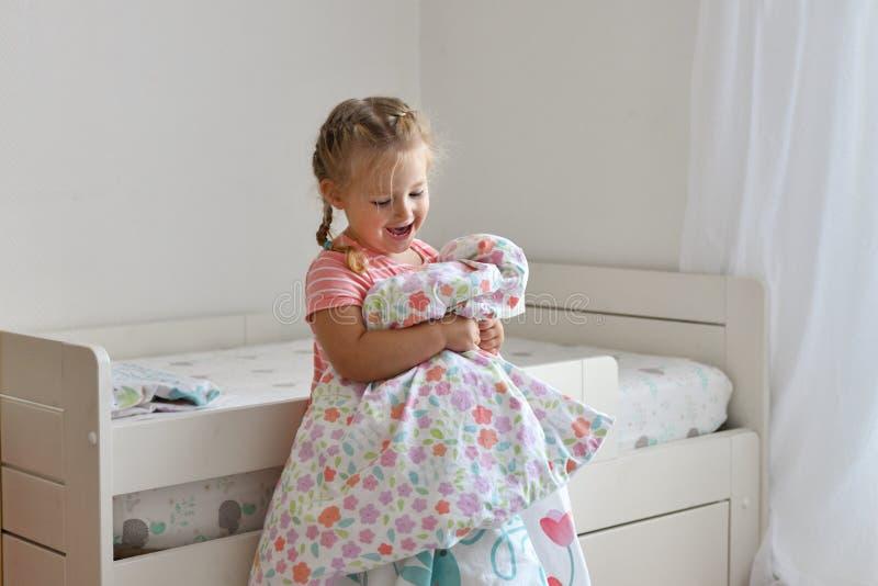 Uma menina faz uma cama na sala de crianças imagens de stock