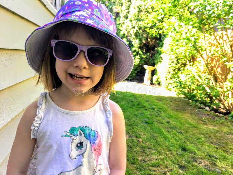Uma menina feliz da criança de 5 anos que sorri no quintal em um dia ensolarado O verão começou Est? vestindo uma camisa do unic? foto de stock