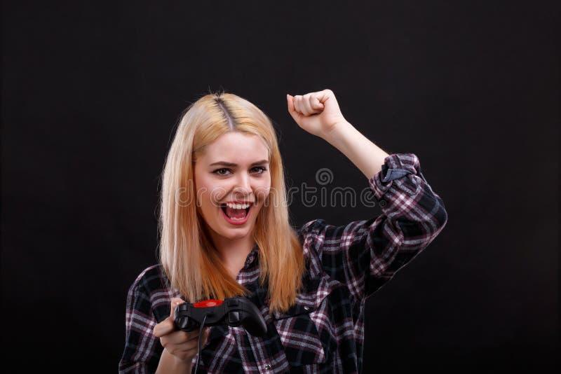 Uma menina feliz em uma camisa quadriculado, em posses um manche e em mão alegremente do levantamento apertou o punho acima imagens de stock