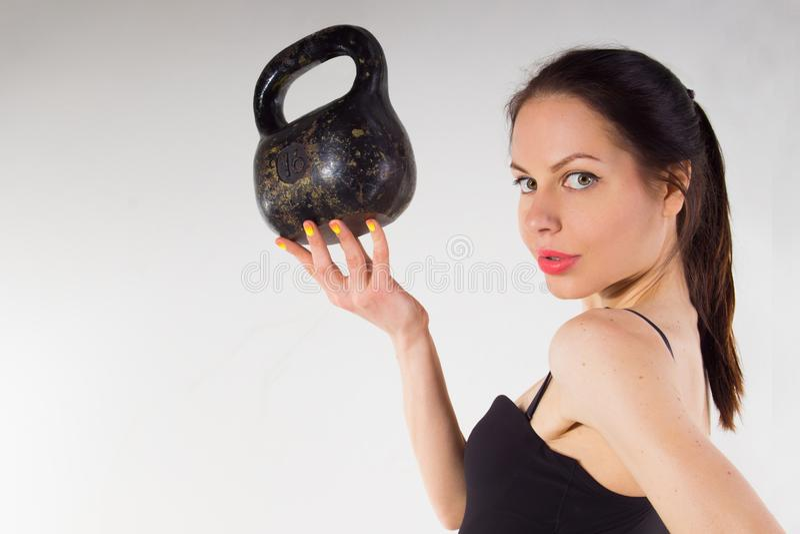 Uma menina fina com um peso em sua mão foto de stock royalty free