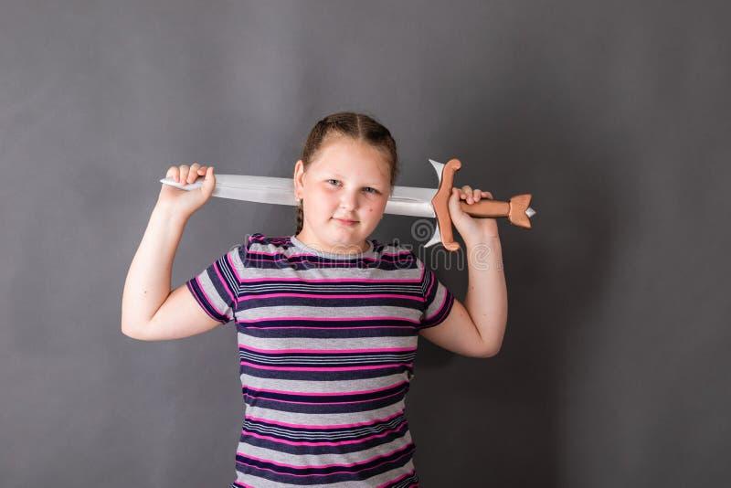 Uma menina forte, robusta da idade escolar com a espada em seus braços fotos de stock royalty free
