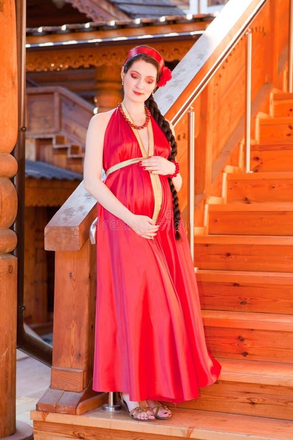 Uma menina grávida nova que está nas escadas fotos de stock royalty free