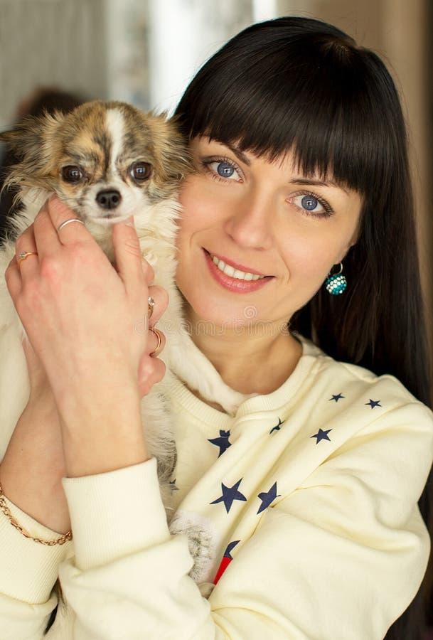 Uma menina guarda um cão em seus braços fotos de stock royalty free