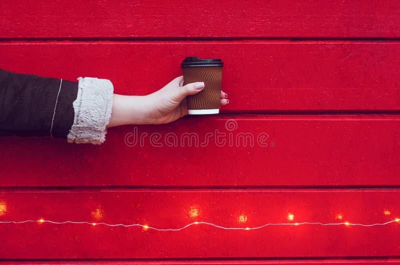 Uma menina guarda uma xícara de café ou um chá fotos de stock