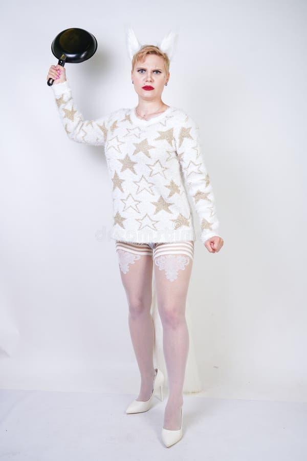 Uma menina irritada com cabelo louro curto em uma camiseta macia com orelhas da pele mulher positiva má do tamanho com a frigidei foto de stock