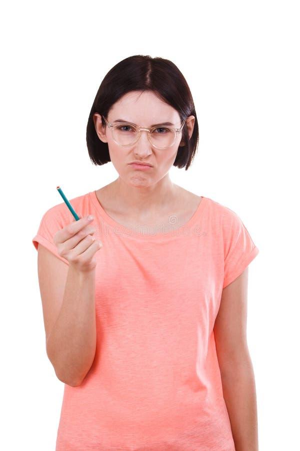 Uma menina irritada com um lápis em sua mão em um branco isolou o fundo imagens de stock