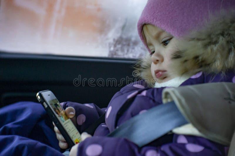 Uma menina joga no telefone ao sentar-se em um carro em um assento da criança fotografia de stock