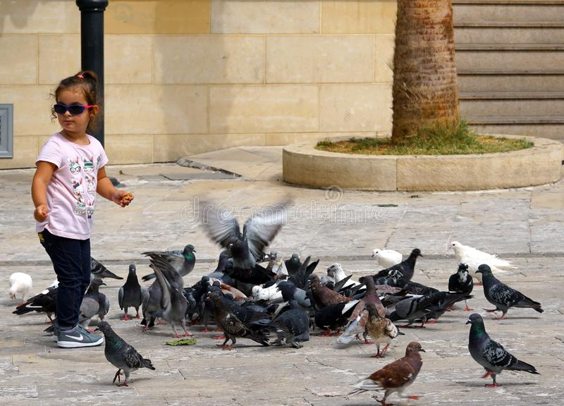 Uma menina joga pombos de alimentação em Heraklion imagem de stock royalty free