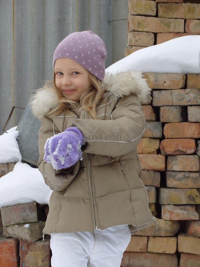 Uma menina joga um snowball imagem de stock royalty free