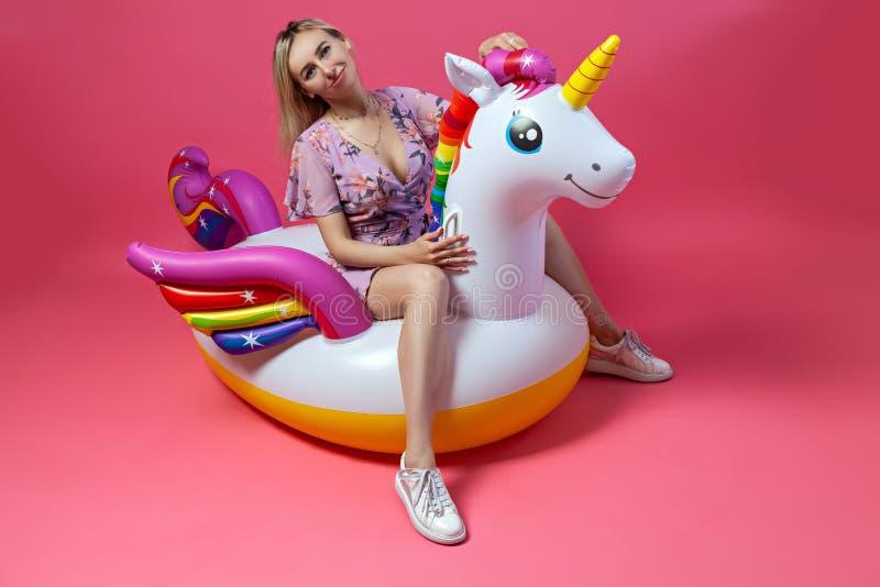 Uma menina loura bonita no sundress 'sexy' com pés magros nas sapatilhas brancas senta-se em um unicórnio multi-colorido inflável imagens de stock royalty free