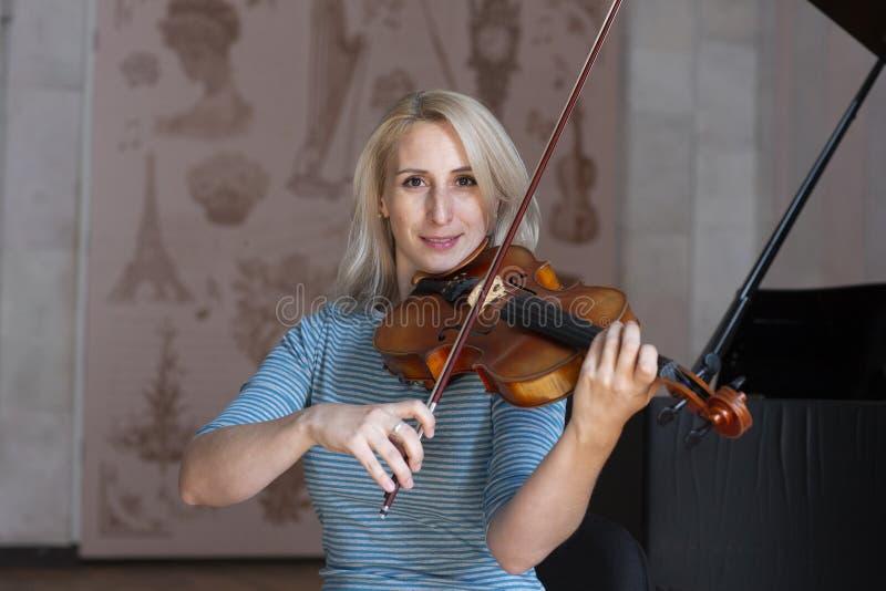 Uma menina loura bonita no vestido preto com bordos vermelhos joga um violino imagens de stock royalty free