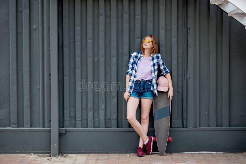Uma menina loura bonita que veste o short quadriculado da camisa e da sarja de Nimes está estando na frente da parede preta com u fotografia de stock