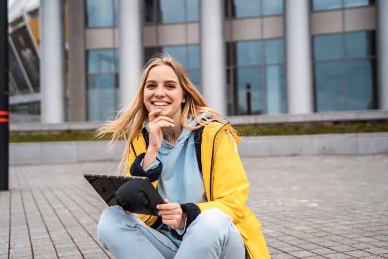 Uma menina loura bonita senta-se em uma rua e usa-se uma tabuleta fotografia de stock royalty free