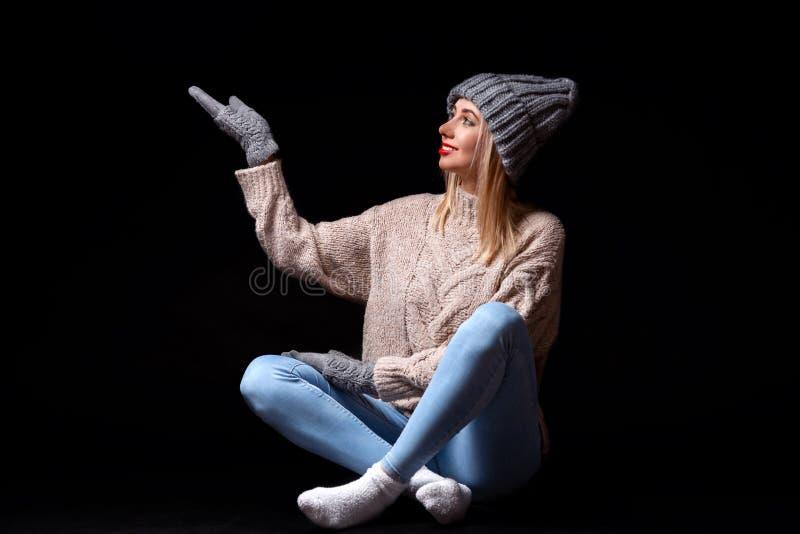 Uma menina loura de sorriso em luvas feitas malha cinzentas, o chapéu e a camiseta que sentam-se no assoalho preto com pés cruzad fotografia de stock