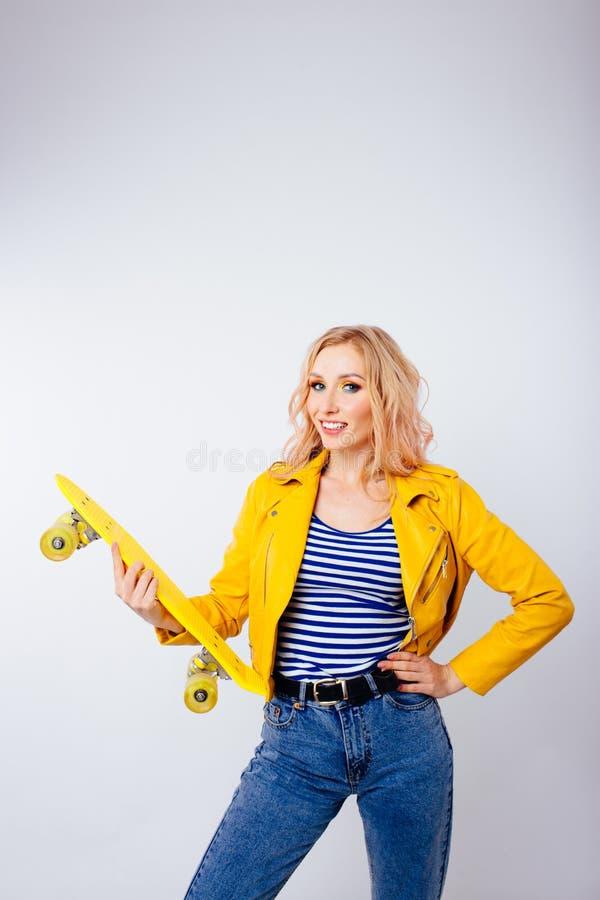 Uma menina loura delgada com um patim amarelo em suas m?os em um fundo branco isolado fotografia de stock