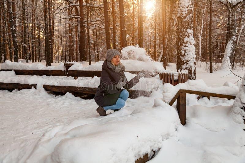 Uma menina loura em um chapéu cinzento e em um escuro - o casaco azul no inverno na floresta está sentando-se em um monte de neve foto de stock