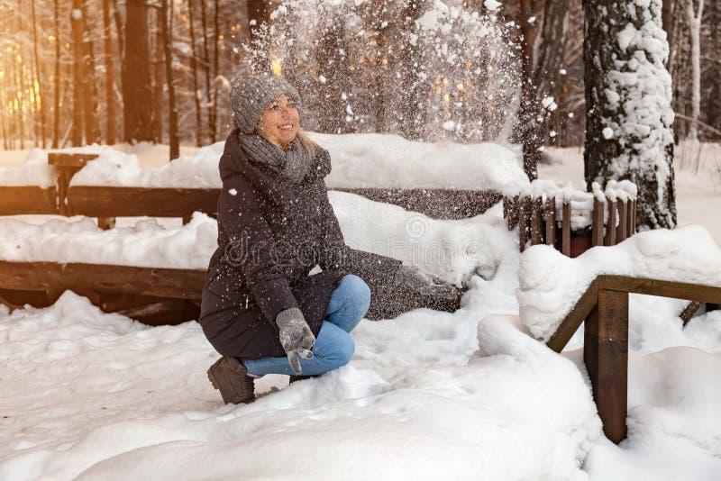Uma menina loura em um chapéu cinzento e em um escuro - o casaco azul no inverno na floresta está sentando-se em um monte de neve foto de stock royalty free