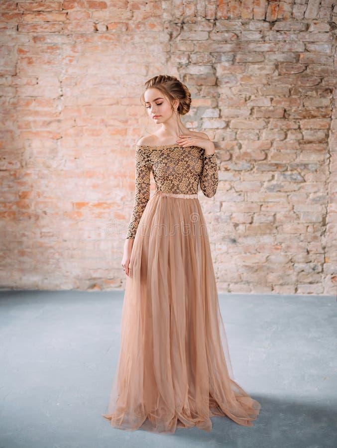 Uma menina loura está levantando em um vestido arenoso, marrom macio com uma parte superior do laço e com uma saia suntuoso do tu imagens de stock
