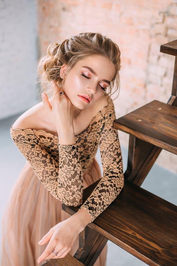 Uma menina loura está levantando em um vestido arenoso, marrom macio com uma parte superior do laço e com uma saia do tule A imag imagem de stock