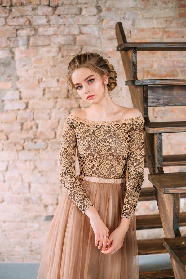 Uma menina loura está levantando em um vestido arenoso, marrom macio com uma parte superior do laço e com uma saia do tule A imag fotos de stock