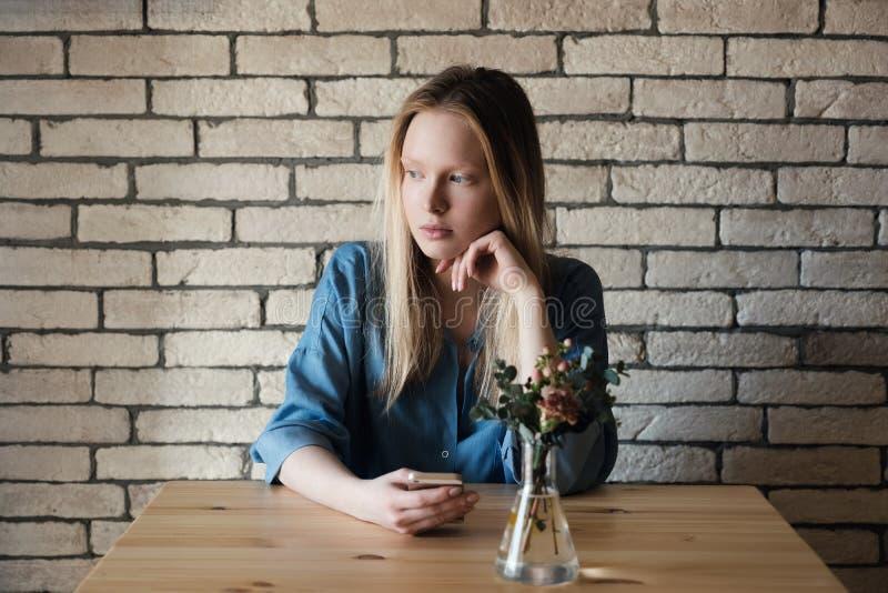 Uma menina loura está sentando-se em uma tabela que guarda um telophome em seu h fotografia de stock