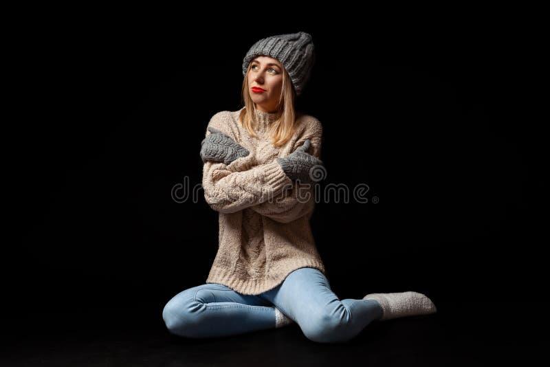 Uma menina loura nas luvas, no chapéu cinzento e na camiseta feitos malha sentando-se no assoalho preto com os braços dobrados e  foto de stock