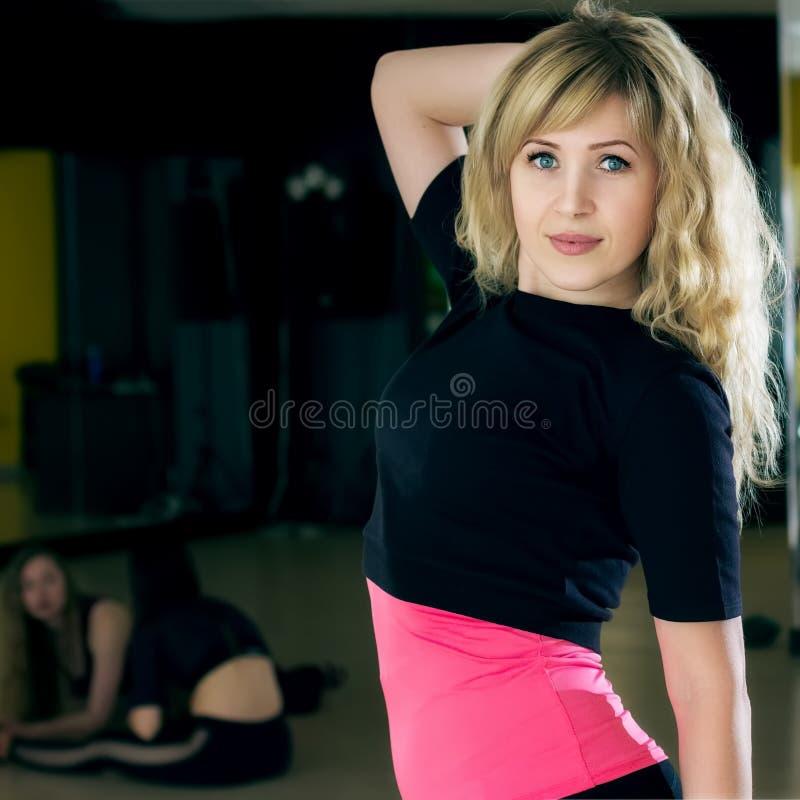 Uma menina loura nova bonita da aparência caucasiano que levanta após um exercício por pilates em um preto e em uma parte superio imagem de stock royalty free