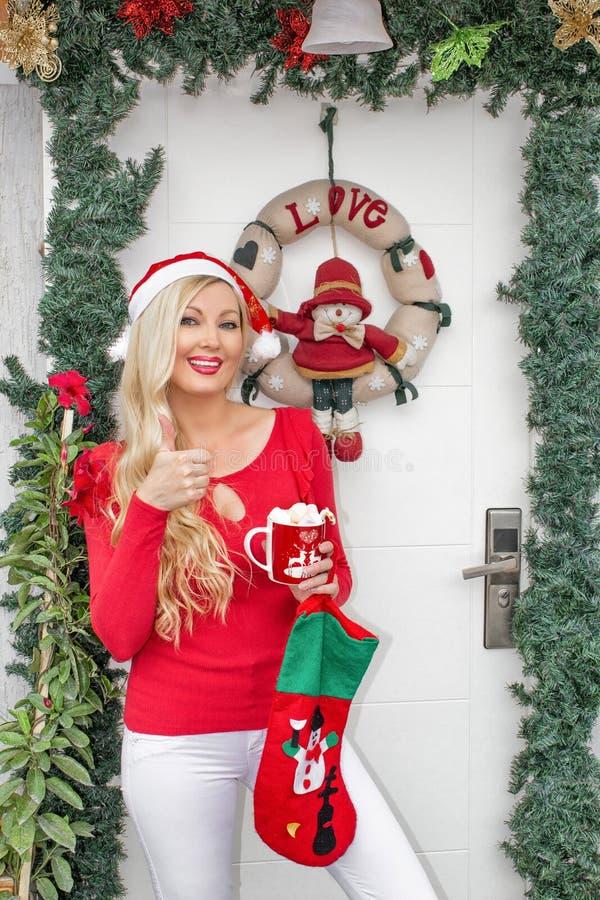 Uma menina loura nova bonita no tampão de uma Santa está na porta da rua decorada com uma grinalda e ramos do abeto vermelho imagens de stock royalty free