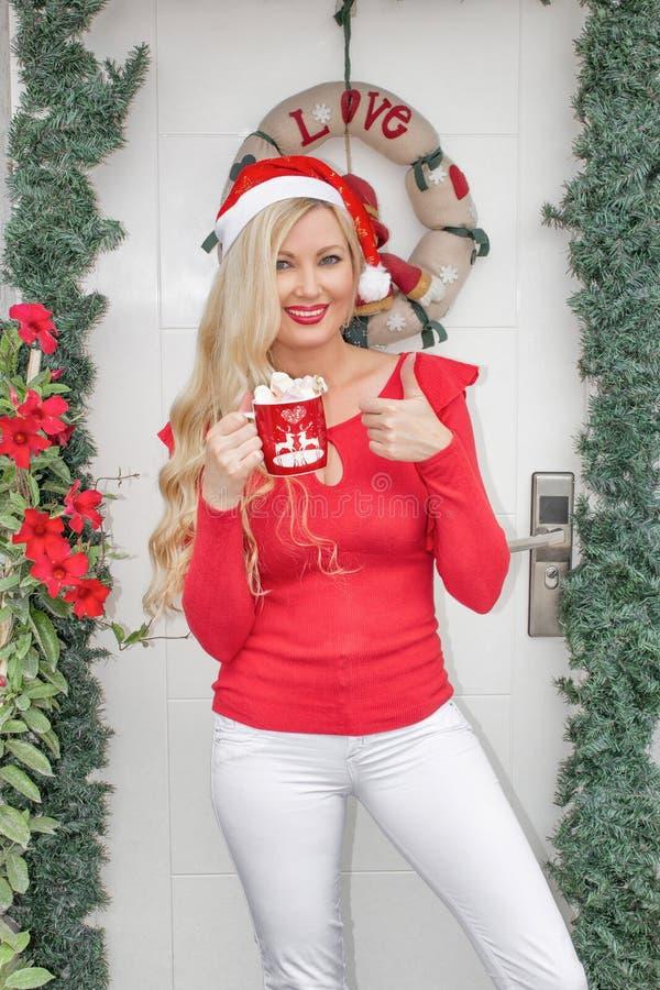 Uma menina loura nova bonita no tampão de uma Santa está na porta da rua decorada com uma grinalda e ramos do abeto vermelho fotos de stock