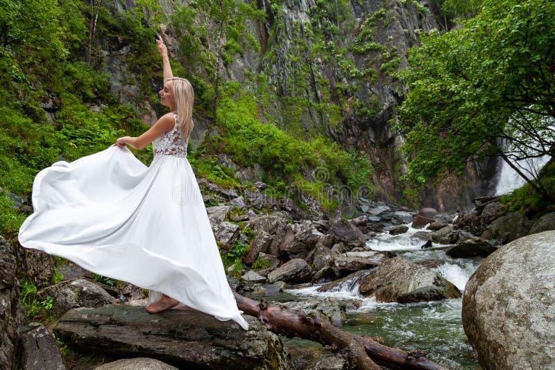 Uma menina loura nova em uma pose elegante levanta um vestido do boudoir nas montanhas contra uma cachoeira e as pedras que levan fotografia de stock