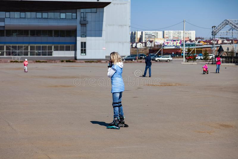 Uma menina loura nova em um casaco azul está patinando em torno do quadrado para caminhadas e do resto em um dia de mola claro foto de stock royalty free