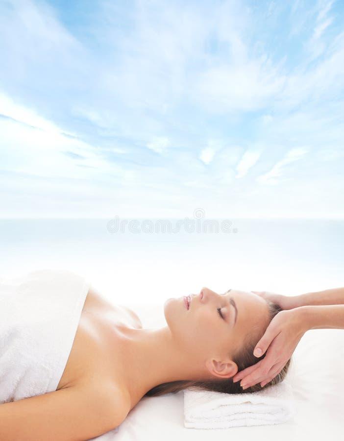 Uma menina loura nova em um procedimento principal da massagem fotografia de stock