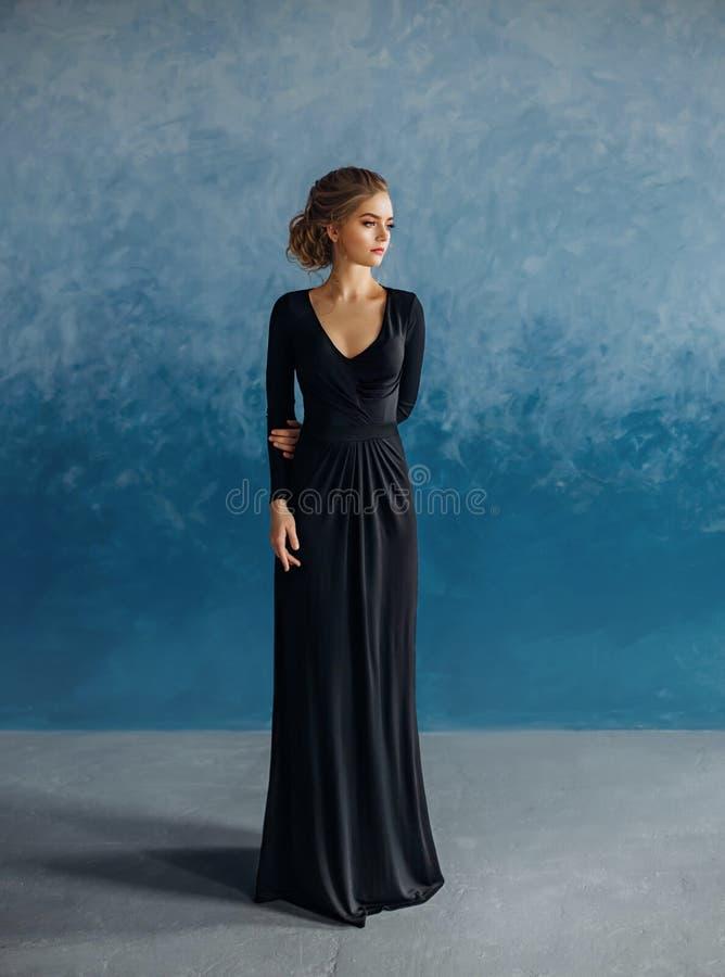 Uma menina loura nova em um vestido preto restrito, discreto, modesto, elegante, longo Composição natural delicada Bonito imagens de stock