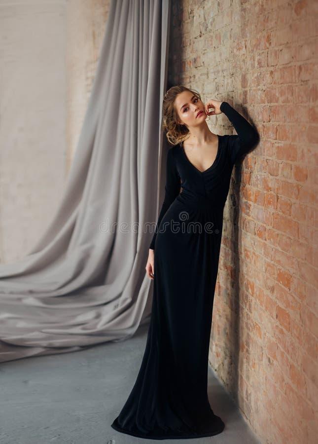 Uma menina loura nova em um vestido preto restrito, discreto, modesto, elegante, longo Composição natural delicada Bonito fotos de stock royalty free