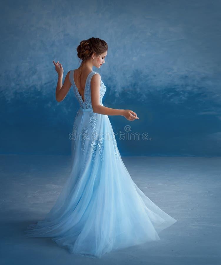 Uma menina loura nova está girando em um vestido azul luxuoso com um aberto para trás O fundo é uma parede dos azul-céu imagens de stock