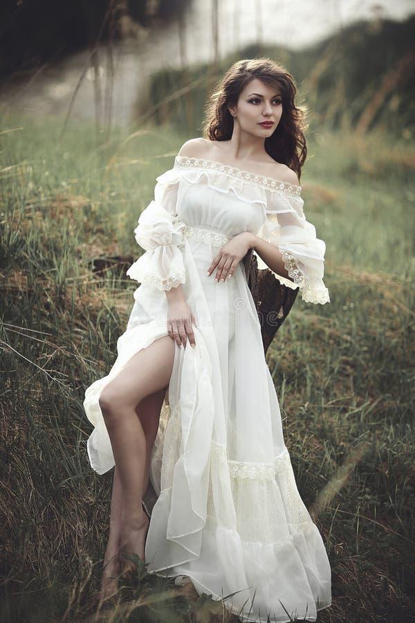 Uma menina macia bonita em um vestido branco senta-se em um coto de árvore foto de stock royalty free